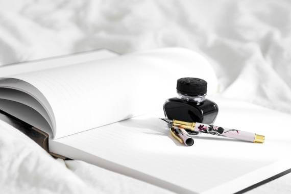 fountain pen and inkwell sitting on open notebook