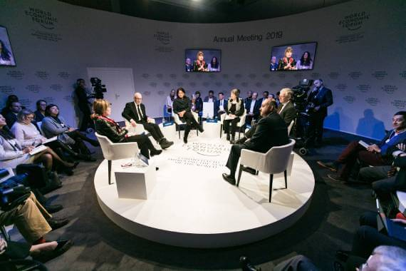Participants at World Economic Forum sitting in a round on a raised platform