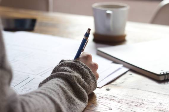 Hand holding pen on paper to edit content with blurred coffee cup in the background