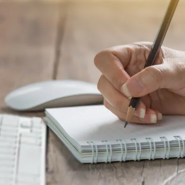 Hand holding pencil above a notebook, ready to start copywriting. Keyboard, mouse, and coffee cup in background