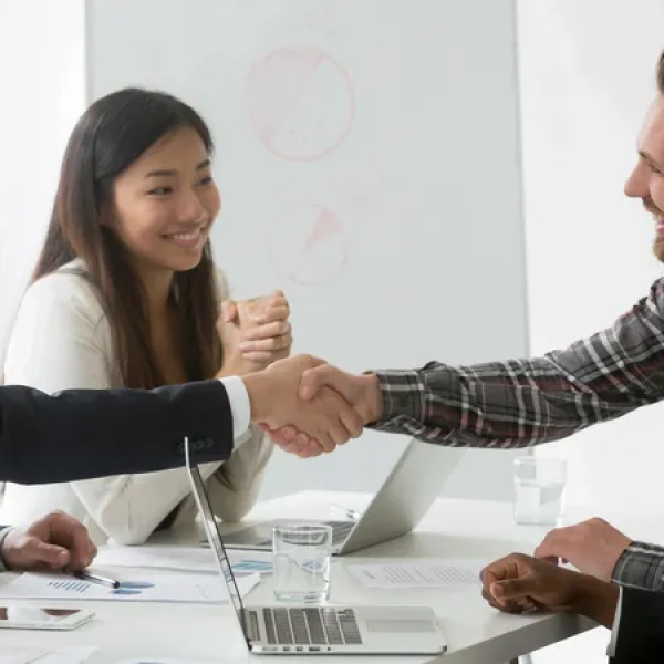 Five business people smiling, two of them shaking hands