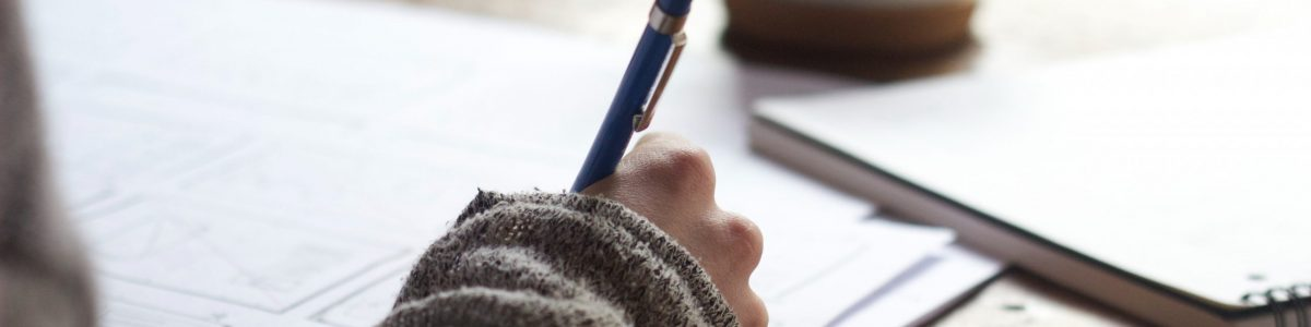 Hand holding pen on paper to edit content, blurred coffee cup in the background
