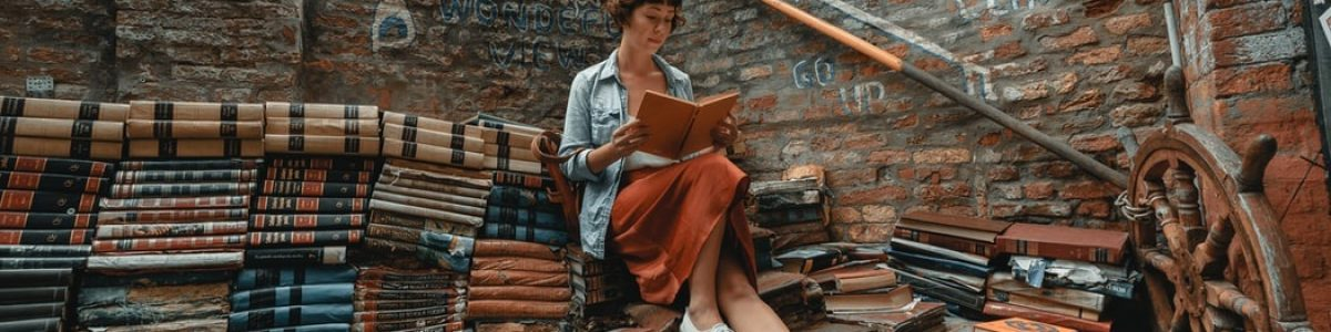 Woman sitting reading, surrounded by stacks of books inside a brick walled area. Brick building in the background.