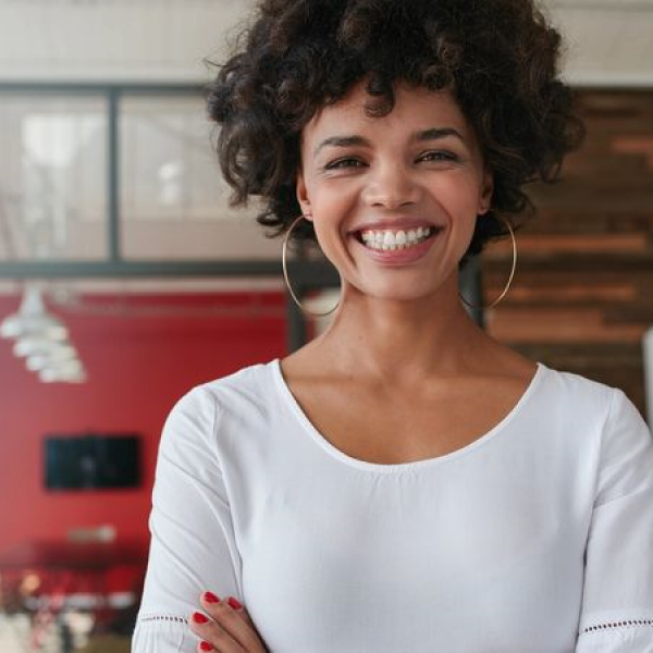 Woman looking at camera with a big smile, man standing in a marketing office in the background