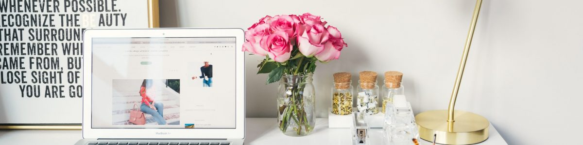 Desk with lamp, flowers, glasses books, phone, and laptop showing imagery on screen